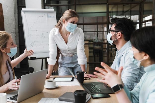 Imprenditrice con mascherina medica durante un incontro professionale con i suoi colleghi