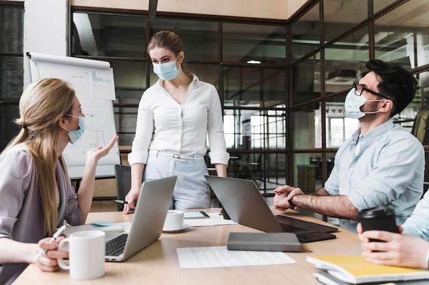 Imprenditrice con mascherina medica durante un incontro professionale