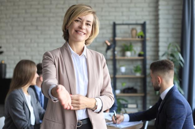 Imprenditrice con una mano aperta pronta per la stretta di mano in ufficio.