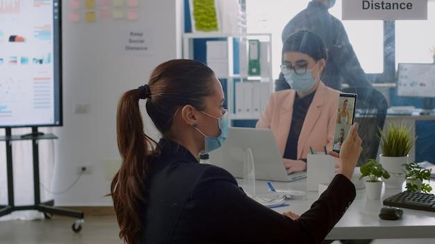 Donna d'affari con maschera facciale di protezione che parla in webcam con manager esecutivo seduto nell'ufficio della società commerciale. colleghi nel rispetto della distanza sociale per prevenire il contagio da covid19