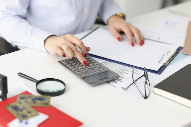 Donna di affari con il manicure rosso che conta sulla calcolatrice nel calcolo del primo piano dell'ufficio di a