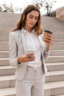 Donna di affari con smartphone e tazza di caffè sulle scale
