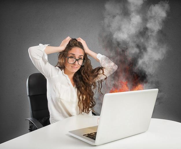 La donna di affari con l'espressione sollecitata esamina il computer portatile in fiamme