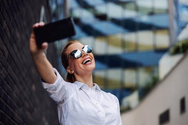 Imprenditrice con occhiali da sole in piedi fuori e prendendo selfie. esterno del centro affari.
