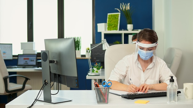 Imprenditrice con visiera e maschera di protezione che analizza le statistiche finanziarie annuali prendendo appunti negli appunti nel nuovo normale ufficio commerciale. dipendenti che lavorano in azienda rispettando la distanza sociale.