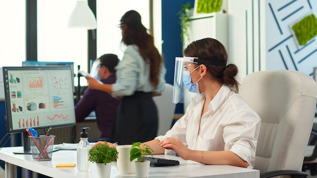 Donna d'affari con visiera e maschera di protezione che lavora nel nuovo normale ufficio finanziario. colleghi che consigliano in background, team aziendale che rispetta la distanza sociale durante la pandemia globale.