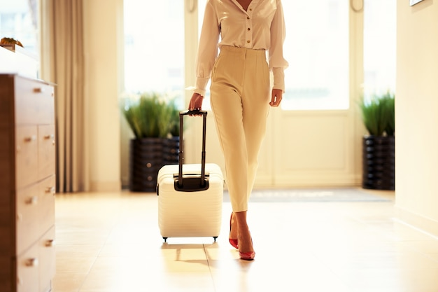 Imprenditrice con valigia bianca nel moderno atrio dell'hotel