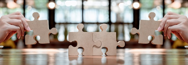 Imprenditrice con puzzle in legno e puzzle per il concetto di successo aziendale. simbolo di lavoro di squadra e successo.