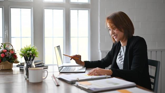 Analisi di lavoro della donna di affari sul computer portatile, sulle finanze di affari e sul concetto di contabilità.