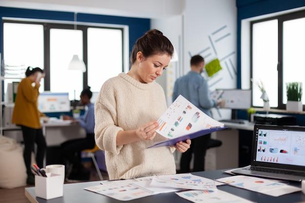 Donna d'affari che lavora alla sua scrivania in ufficio controllando e analizzando il rapporto. imprenditore esecutivo, manager leader in piedi lavorando su progetti con diversi colleghi.