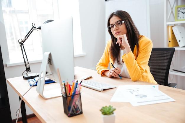 Donna d'affari che lavora al suo posto di lavoro in ufficio