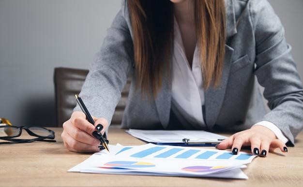 Imprenditrice che lavora con grafici e tabelle in ufficio.