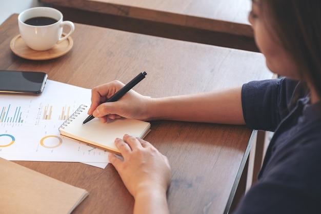 Una donna d'affari scrivendo sul taccuino e lavorando su dati aziendali e documenti sul tavolo in ufficio