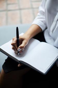 Imprenditrice scrivendo nel pianificatore