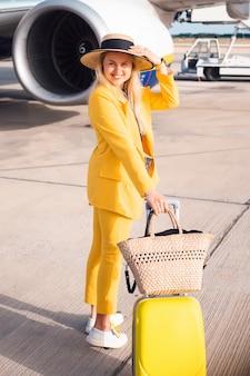 Donna di affari nel soggiorno giallo vicino all'aereo di aria