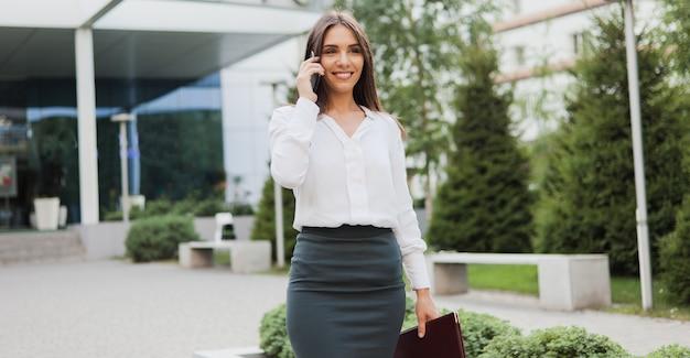 Imprenditrice. giovane manager femminile che indossa una gonna e una camicetta parlando al telefono