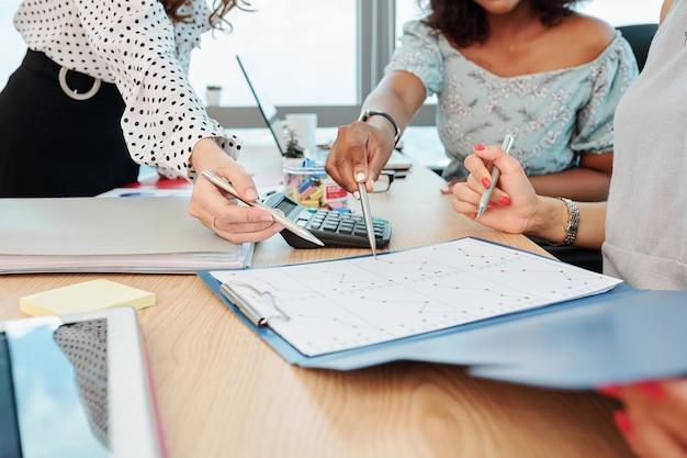 Donne di affari che indicano il grafico delle statistiche di vendita
