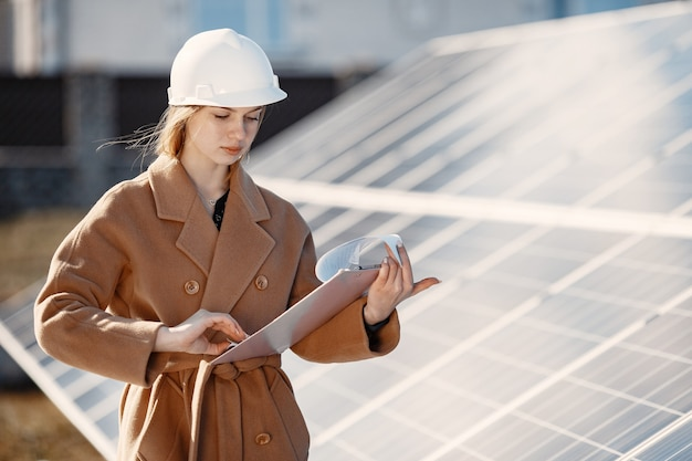 Imprenditrici che lavorano al controllo delle apparecchiature presso la centrale elettrica solare. con la lista di controllo della compressa, donna che lavora all'aperto ad energia solare.