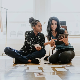 Donne d'affari che lavorano insieme utilizzando una tavoletta digitale