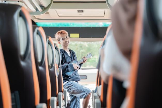 Un suonatore ambulante canta mentre usa uno strumento ukulele ei passeggeri dell'autobus battono le mani lungo la strada