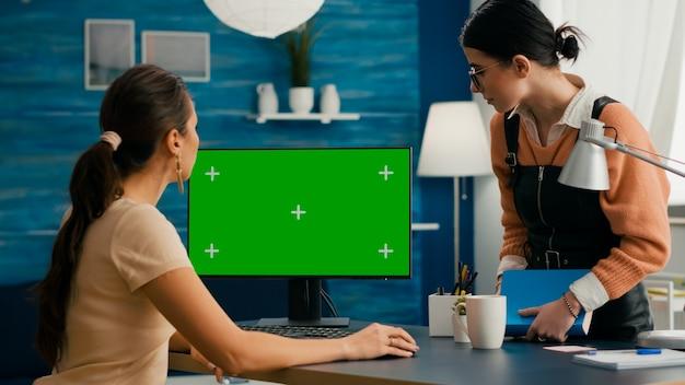 Donna d'affari che parla con il giovane collega della rete internet che mostra sul computer con mock up chroma key schermo verde. femmina caucasica che utilizza un pc desktop isolato nell'ufficio di casa