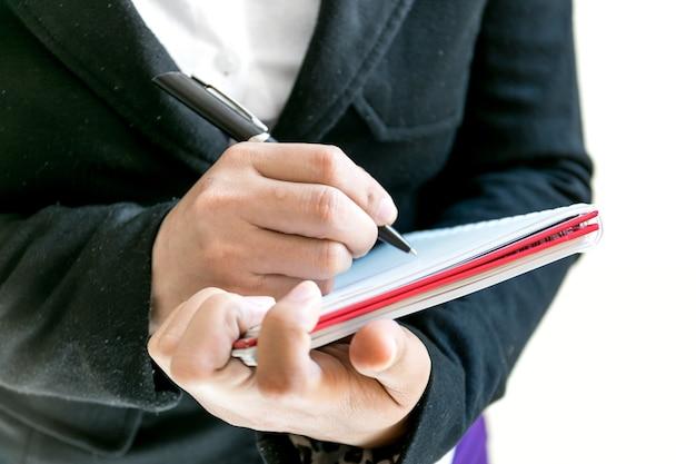 Donna di affari che scrive la parola su un taccuino.