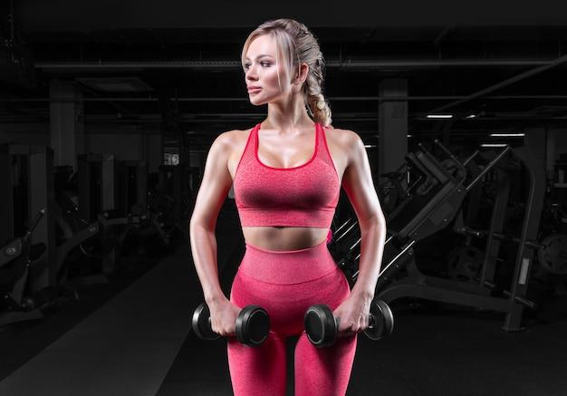 Bionda tettona in tuta rosa in posa in palestra con manubri. concetto di fitness.