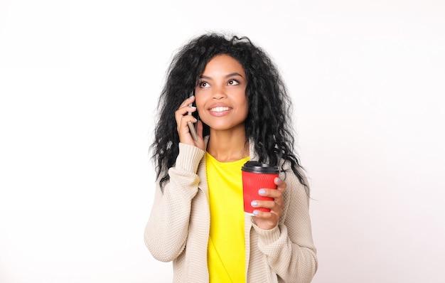 Impegnata donna afroamericana in maglione beige sta parlando al telefono mentre tiene una tazza di caffè di carta rossa nella mano sinistra, guardando l'angolo in alto a sinistra e sorridendo