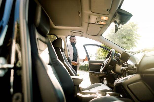 Occupato giovane africano in tuta salire in macchina. giovane uomo d'affari felice che ottiene dentro la sua automobile. uomo africano in tuta fare un passo nel suo veicolo.