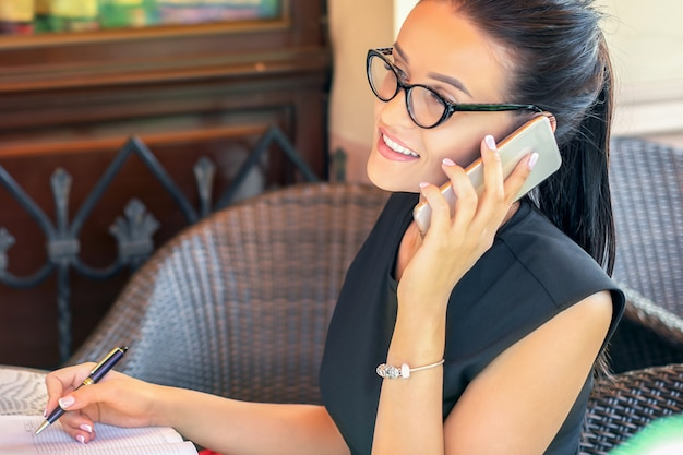 La donna di affari occupata sta parlando al telefono