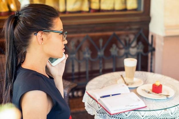 I vetri da portare della donna occupata di affari sta parlando sullo smart phone e stanno lavorando al caffè.