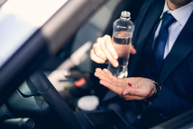Uomo d'affari impegnato seduto nella sua macchina e prendendo tablet mentre ha un forte mal di testa dopo l'incontro