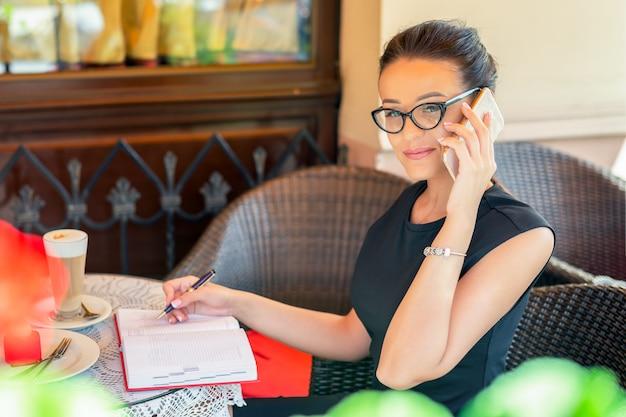 I vetri da portare della donna di affari occupata stanno parlando al telefono mentre lavoravano al caffè.