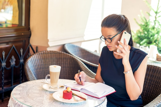 Vetri da portare occupati della donna di affari che lavorano in un caffè che parla al telefono.