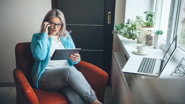 Occupato donna caucasica con capelli biondi e occhiali da vista parlando al telefono da casa utilizzando un tablet