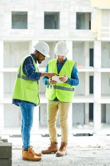 Collaboratori impegnati che discutono piano dei lavori di costruzione