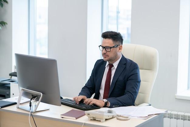 Direttore impegnato in abito elegante digitando e guardando lo schermo del computer