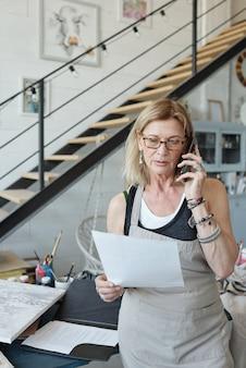 Artista femminile impegnato in grembiule e occhiali da vista controllando lo schizzo e discutendo l'immagine con il cliente per telefono