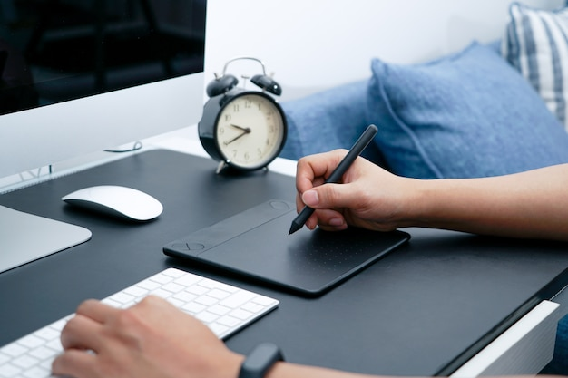 Grafico impegnato che lavora al computer con il mouse digitale