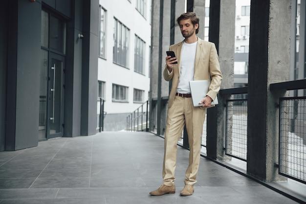 Uomo bello occupato in abito formale alla moda che tiene in una mano uno smartphone moderno e un laptop portatile in un altro. uomo d'affari barbuto in piedi vicino al centro ufficio