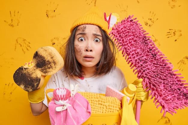 La casalinga occupata guarda con un'espressione preoccupata e stressata fa le faccende domestiche per tenere le attrezzature per la pulizia o gli strumenti domestici vicino al cesto della biancheria isolato sul muro giallo dello studio