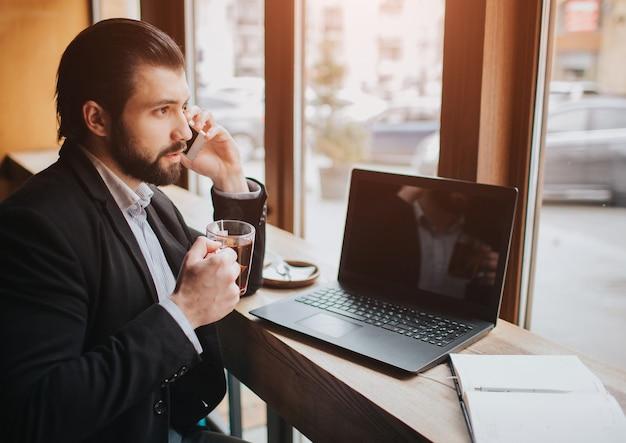 L'uomo impegnato ha fretta, non ha tempo, farà uno spuntino mentre è in movimento. lavoratore che mangia, beve caffè, parla al telefono, allo stesso tempo. uomo d'affari che fa più attività.
