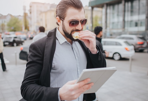L'uomo impegnato ha fretta, non ha tempo, sta andando a mangiare uno spuntino in viaggio. lavoratore che mangia, beve caffè, parla al telefono, allo stesso tempo. uomo d'affari che fa più compiti.
