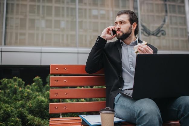 L'uomo impegnato ha fretta, non ha tempo. lavoratore che mangia e che lavora con i documenti sul computer portatile allo stesso tempo. uomo d'affari che fa più compiti. uomo d'affari multitasking.