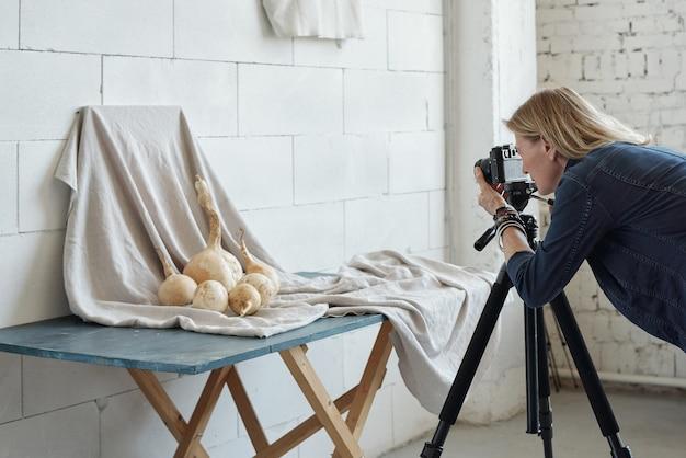 Impegnato fotografo maturo utilizzando la fotocamera sul treppiede mentre si fa la foto creativa di cibo in studio