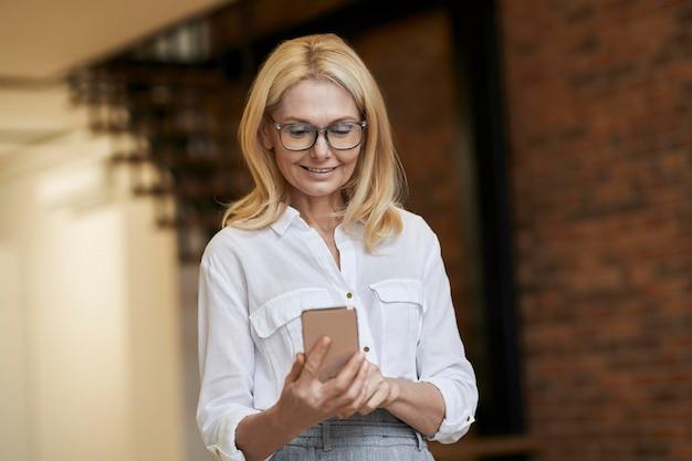 Donna matura impegnata con capelli biondi e occhiali che usa il suo smartphone mentre fa una videochiamata