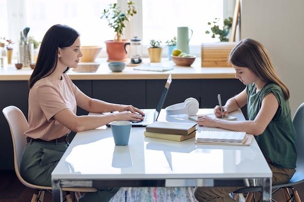Madre di mezza età occupata che scrive sul computer portatile mentre sua figlia fa i compiti a un tavolo con lei