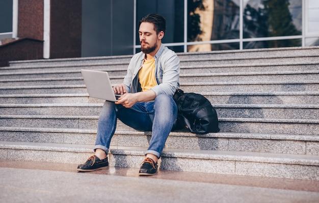 Uomo moderno occupato che si siede sulle scale e lavora con il computer portatile