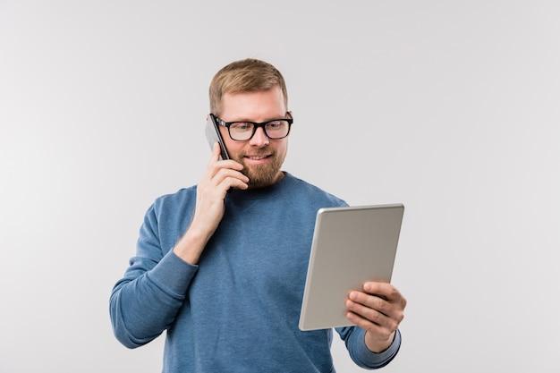 Direttore di ufficio occupato in abbigliamento casual guardando il display del touchpad mentre consulta i clienti sullo smartphone