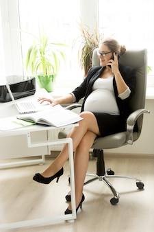 Imprenditrice incinta occupata parlando al telefono in ufficio